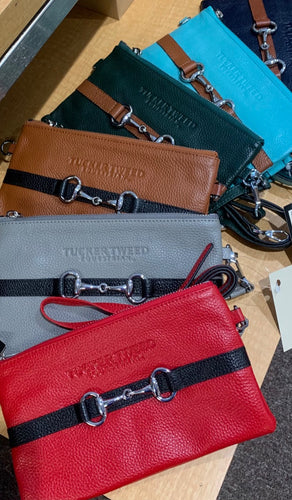 Fanned out display of colorful leather wristlets featuring a contrasting leather stripe with a snaffle bit decoration.