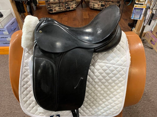 Black english dressage style saddle on a white saddle pad.