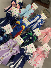 Multiple sets of various colored equestrian show bows.