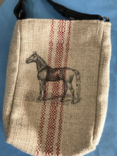 Tan burlap satchel with red stripes down the center and a black sketched horse,  The shoulder strap of the satchel purse is real braided leather equestrian reins.