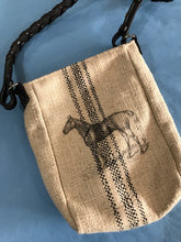 Tan burlap satchel with black stripes down the center and a black sketched horse,  The shoulder strap of the satchel purse is real braided leather equestrian reins.