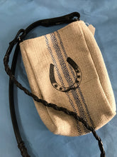 Tan burlap satchel with blue stripes down the center and a black sketched horseshoe,  The shoulder strap of the satchel purse is real braided leather equestrian reins.
