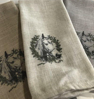 Pictured is a set of three neutral colored kitchen towels.  Each has a bridled horse head within a wreath.