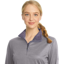 Young equestrian wearing a grey and lavender horseback riding shirt.