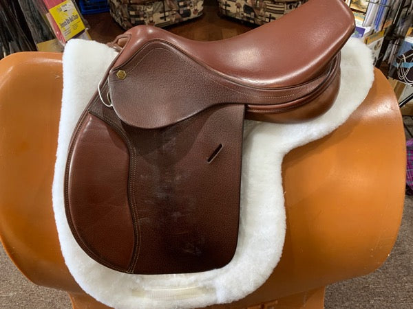 Light brown english style saddle on a white show pad.