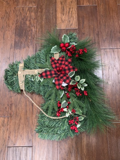 Christmas Holiday wreath shaped like a horse head with a burlap bridle , red plaid bow and holly decoration.