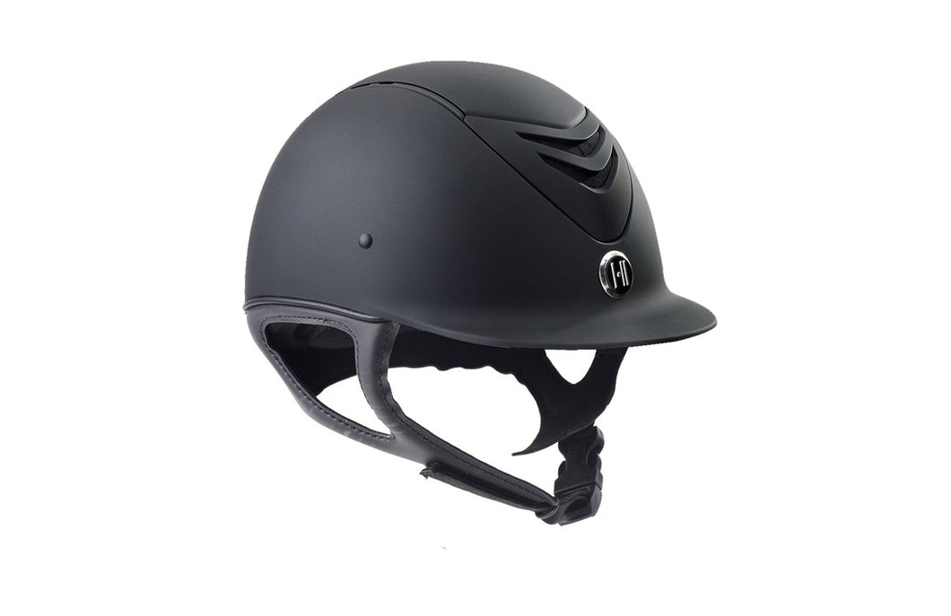 Black equestrian riding helmet.  Black matte helmet with leather look chin strap.  Logo in front center of helmet.