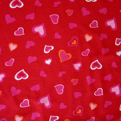 Pink, White, and Orange Hearts on Red Cotton Knit Fabric