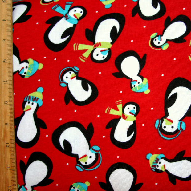 Playful Penguins on Red Cotton Knit Fabric