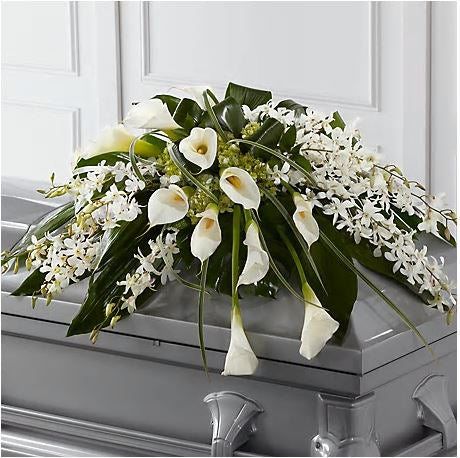 Funeral casket spray with a curtain of orchids and cala lilies.