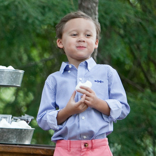 A dapper young man in a Bowen Arrow Button Down enjoying a marshmallow