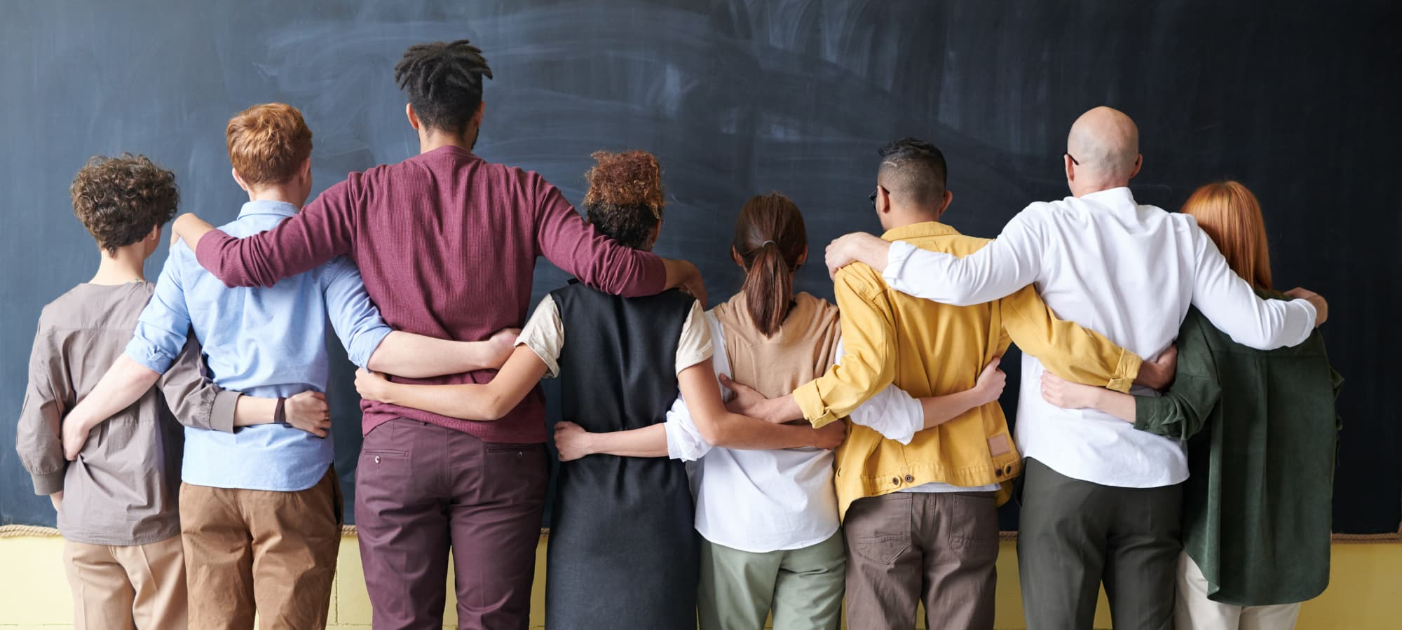 a diverse group of people linking arms in front of a blackboard