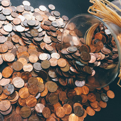 a glass container overflowing with pennies