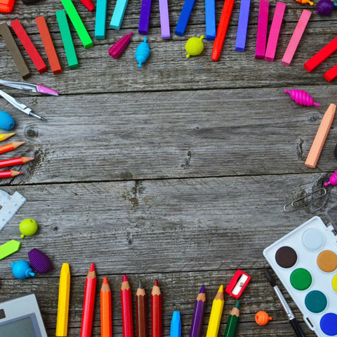 various, multi-colored art supplies on a wooden surface