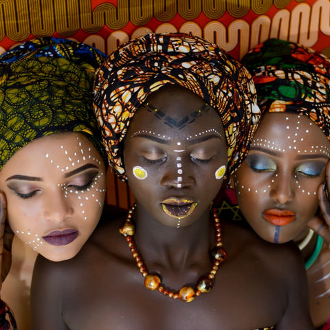 a trio of women in traditional African headdress and face paint