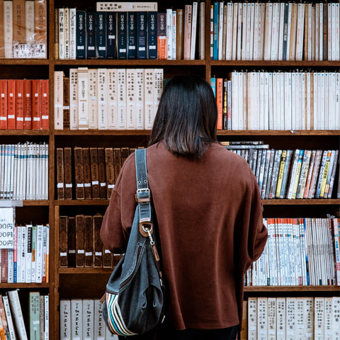 a woman standing in front of a bookshelf