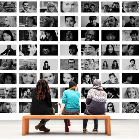 people socializing in front of a wall of black and white portraits