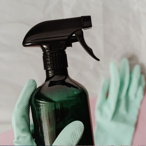 a hand with sanitary gloves holding a bottle of chemical cleaner