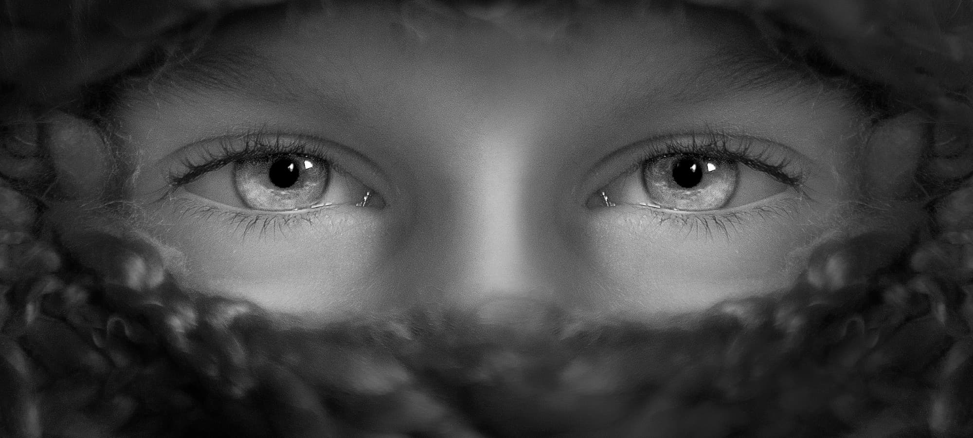 a child's eyes peering out from beneath a blanket