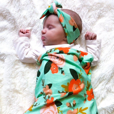 a baby sleeping in a floral print blanket and headband