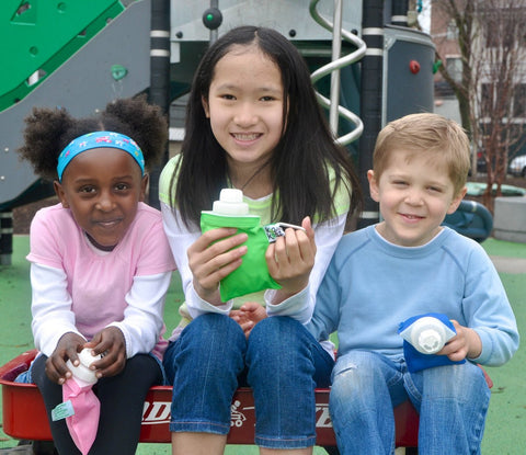 smiling children on a playground eating with reusable lunch pouches