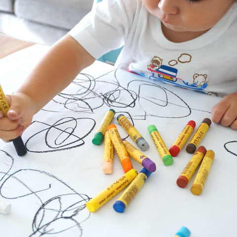 a young child drawing with crayons