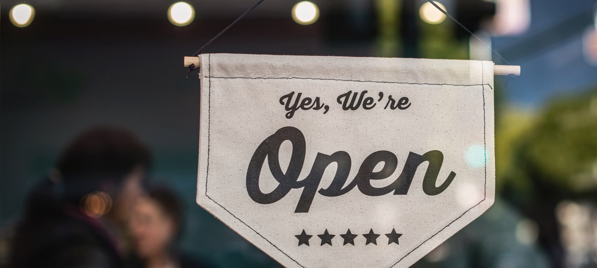 """a storefront sign saying """"yes, we're open"""""""