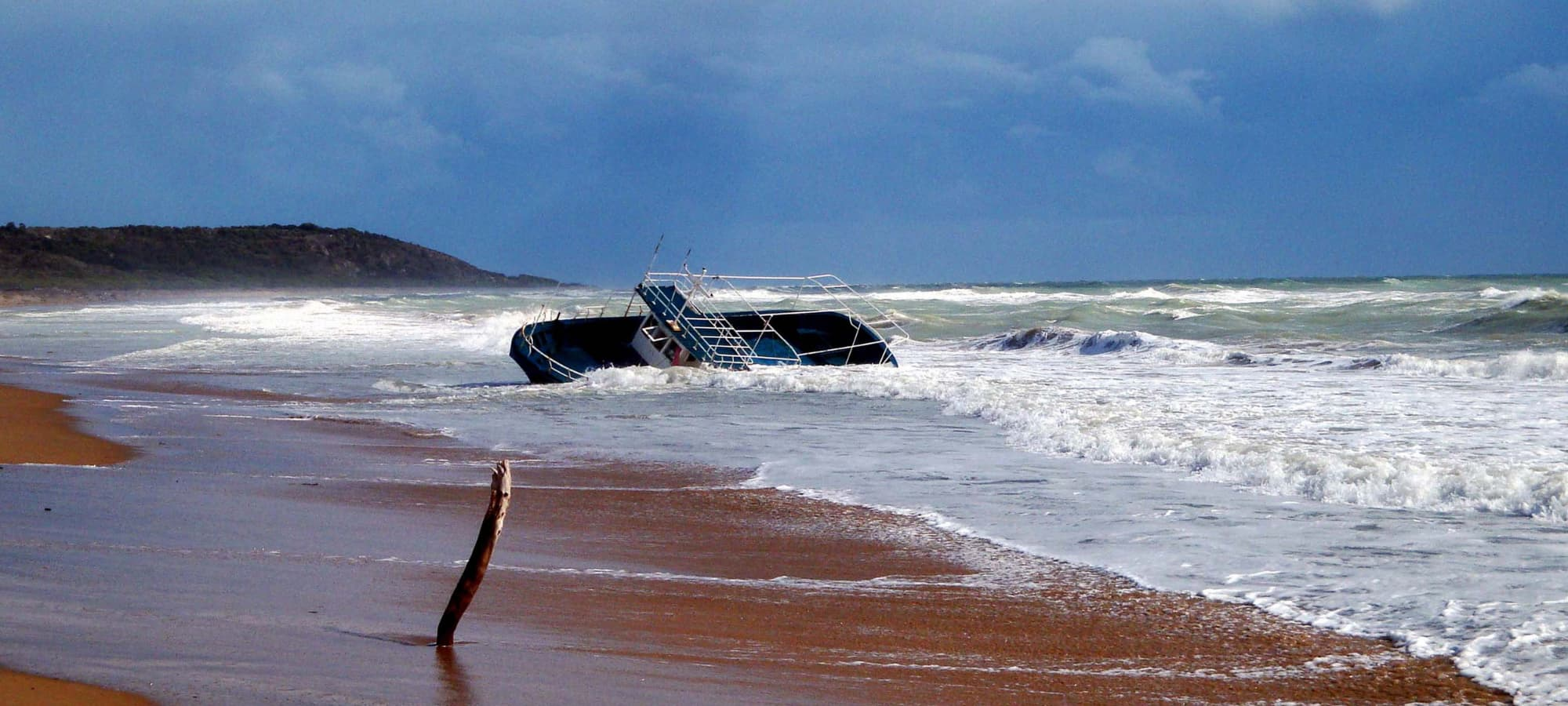 empty refugee boat washed up on a beach