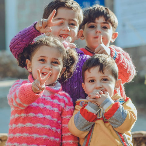 refugee children smiling for a photo