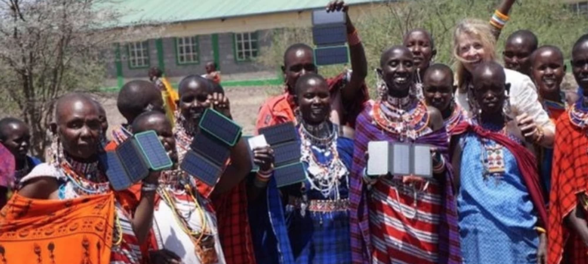 Unite to Light employee presenting solar lights to a group of African women