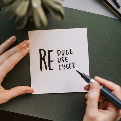"""woman writing a note that says """"reduce, reuse, and recycle"""""""