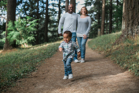 a couple and their toddler out walking on a forest trail