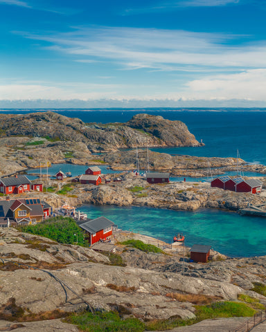 a rocky Swedish coast with small red houses and docks with sailboats