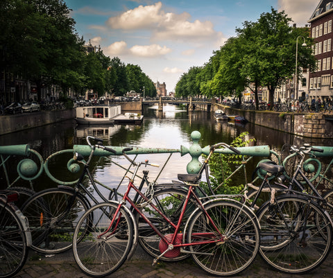 bicycles chained to a bridge rail over an Amsterdam waterway