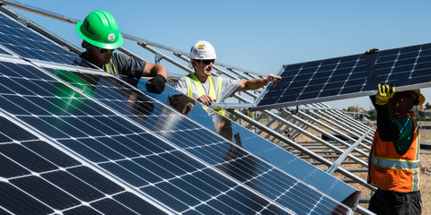 workers in hardhats installing solar panels