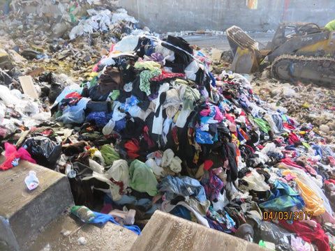 a landfill with large piles of thrown-out clothes