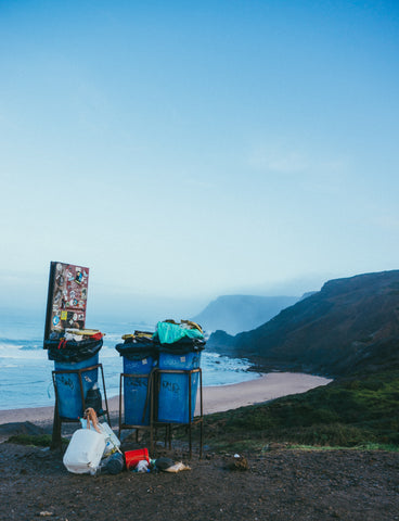 overflowing trash bins on a cliff overlooking a foggy beach