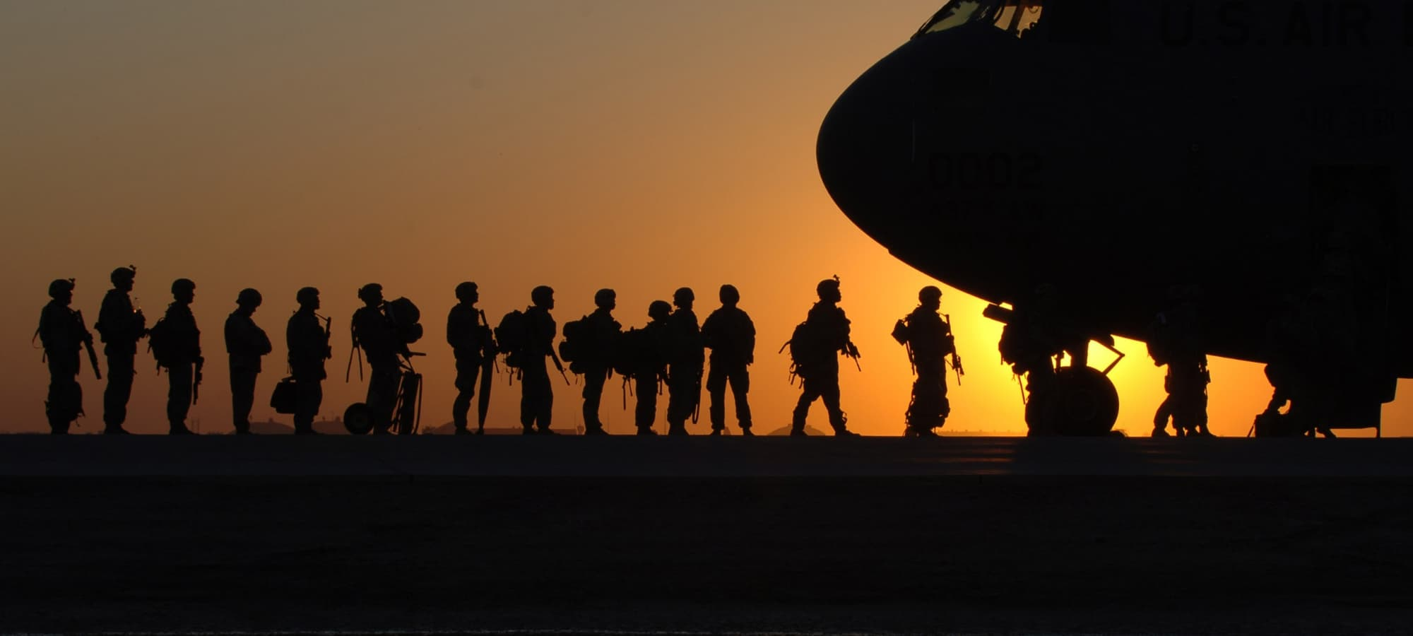 American soldiers boarding a plane at sunset