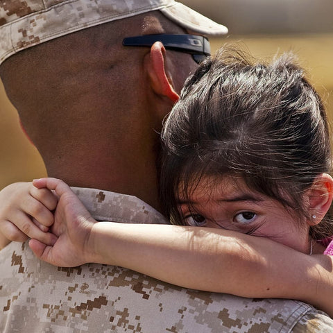 American soldier holing a young girl