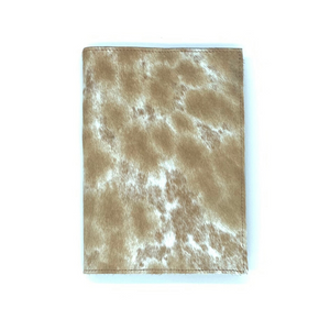 A hand tooled tan and white cowhide journal