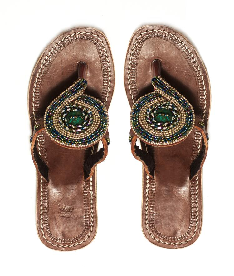 A pair of beaded green sandals with a large bead in the center handmade by artisans to support them with dignified work