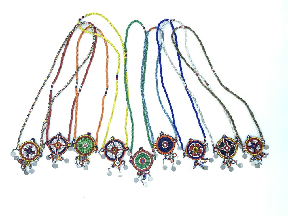 Several beaded necklaces with beaded pendants and hanging metal accents, traditional African jewelry