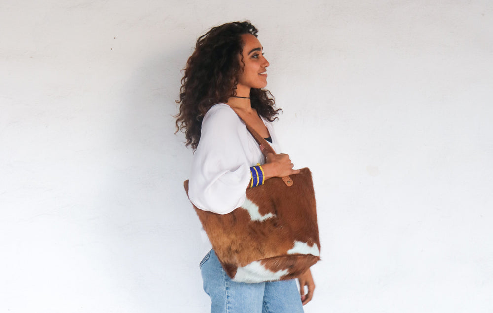 A model holding a tan and white cowhide purse that is creating meaningful work for artisans in Kenya