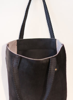 The inside pocket of a unique black cowhide tote bag with black handles