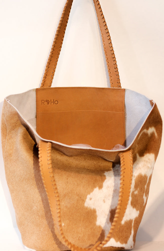 The inside pocket of a tan and white cowhide tote bag with tan handles