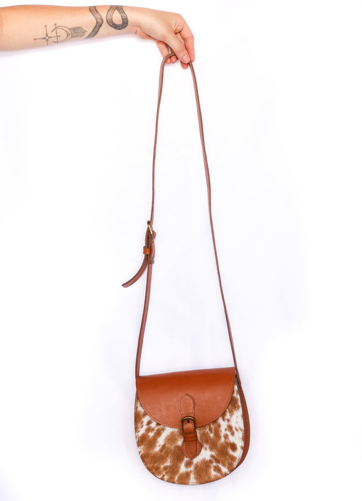 A hand-tooled cowhide crossbody saddle purse in tan and white hide and tan finished leather being held against a white back ground by a model