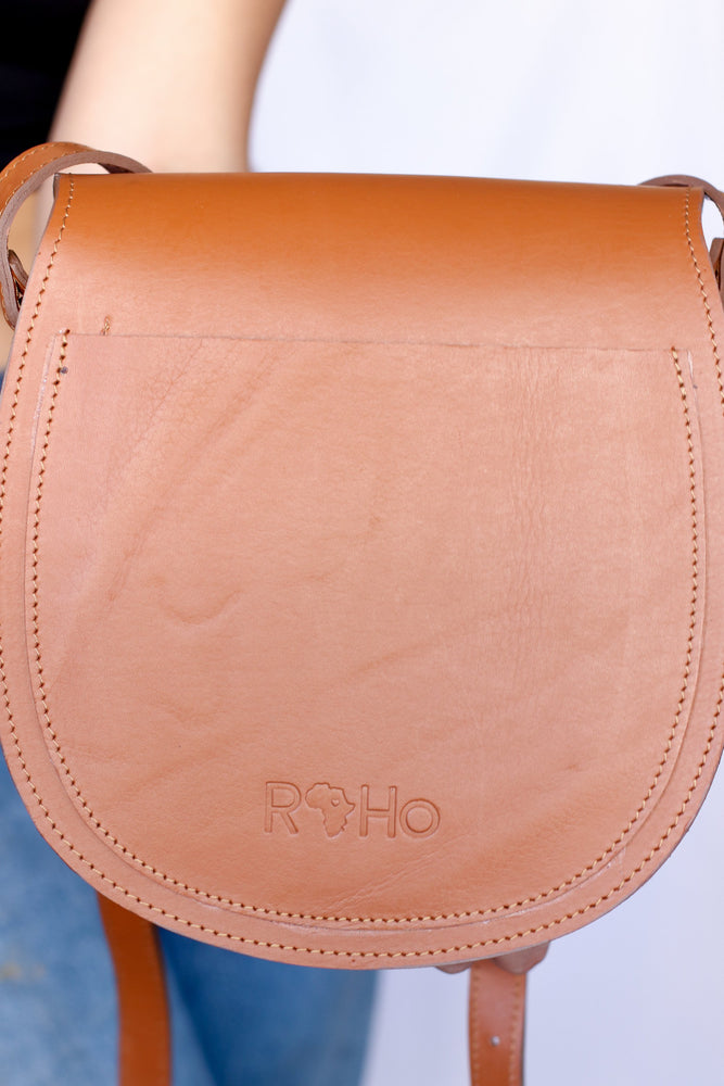 The back of an artisan made cowhide crossbody saddle purse in tan and white hide and tan finished leather being held by a model