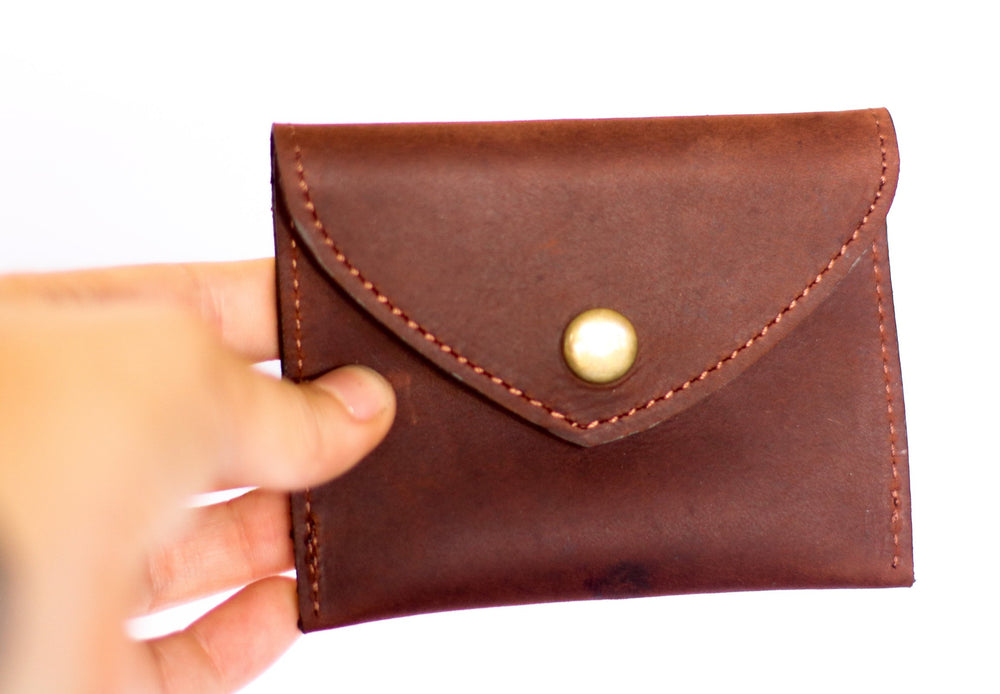 The back of a unique finished brown leather coin purse that creates impact being held by a model