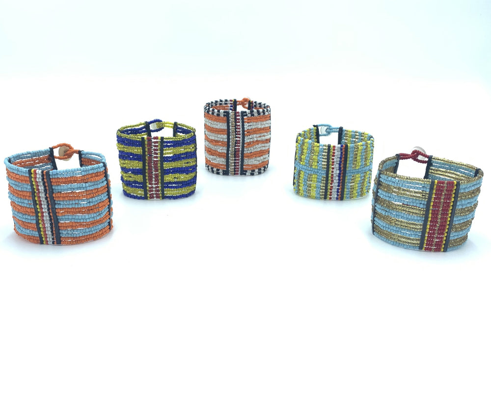 Several beaded cuff bracelets with button cinches