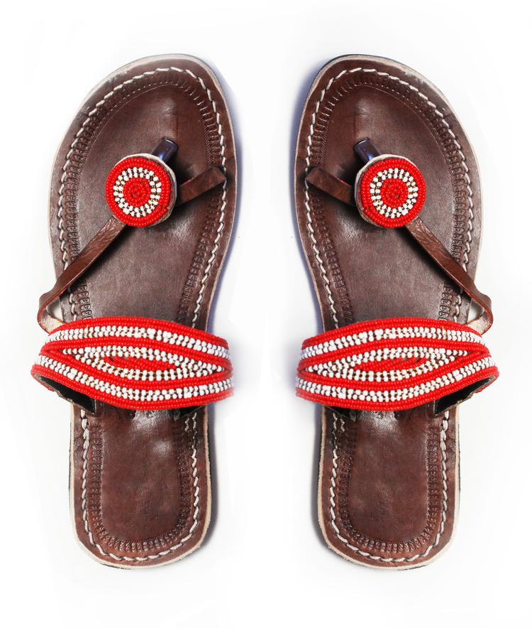 A pair of red and white ethical African beaded leather sandals, the Rafiki sandal, on a white background